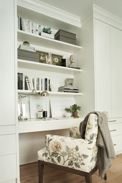 Beautiful home office with built-in shelving and a white floating desk flanked by ceiling height built-in cupboards. The bookshelves are dressed with a mixture of books, framed art and storage boxes. A polished nickel adjustable desk lamp illuminates the desk area. A floral print desk chair layered with a gray throw pulls up to the desk area over light hardwood floors.