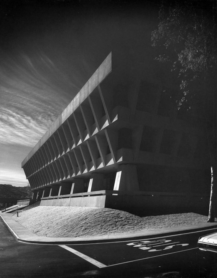 This is a close-up profile view showing the Sunkist Building, located at 14130 Riverside Drive in Sherman Oaks, California (1970). It was designed by A. C. Martin and Associates, a firm with a long and storied history in Los Angeles. For Sunkist, it created a low-rise but monumental late Modern-Brutalist style building of reinforced concrete with recessed windows. It is shaped like an inverted pyramid, wide at the top and tapering in at the base so that it appears to balance on concrete…