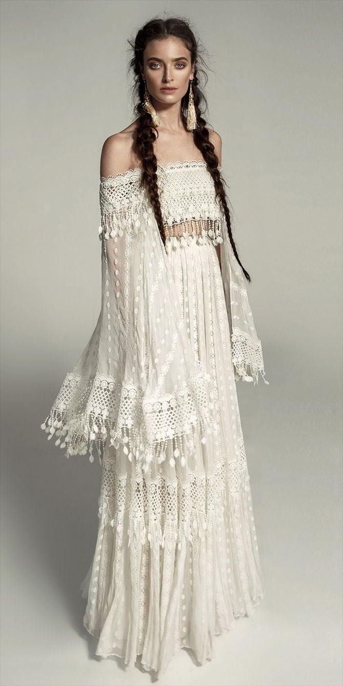 A two-part boho dress. The bottom is made of embroidered silk chiffon combined with a net lace ribbon with cascading pompoms.The top is a strapless tummy cut with sleeves, sewn with double lace ribbon with cascading pompoms. The dress includes a rich and flowing cape of embroidered silk fabric and the same lace ribbon is integrated throughout the entire dress.