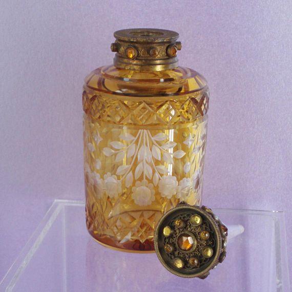 Principios 19thC ámbar corte botella de Perfume de vidrio con un cuello de pedrería y el tapón. El dorado y la orfebrería de filigrana tiene un diseño palmeado y se encuentra con perlas y piedras de ámbar. La botella es ampliamente trabajado con hermosas guirnaldas florales alrededor del panel central. Calidad fabulosa. Yo he asumido las piedras son diamantes y las perlas son imitación.   Medidas: Ht 12.5cm(5), 6cm de diámetro (2 1/4).  Condición: Excelente aún, en su condición original ...