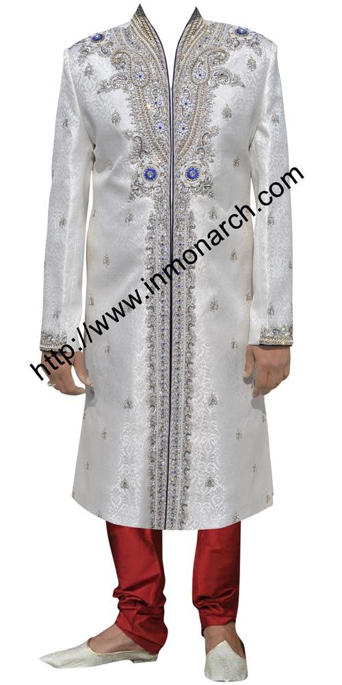 High neck style front open sherwani made from white brocade fabric.It has purple trimmings at front , neck and sleeves cuff edges.Embroidered all over with work on neck ,at bottom panel and sleeves cuffs. It has bottom as chudidar made from dupion fabric in red color as shown.