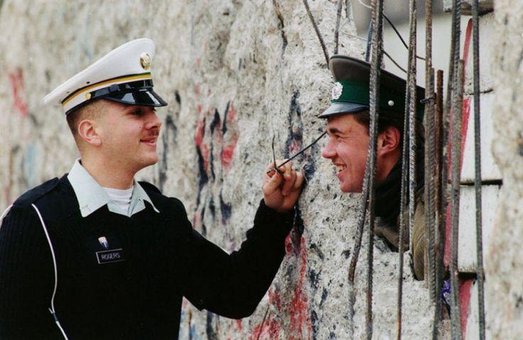 Служащий США Стив Роджерс из Оакланда. Калифорния, разговаривает с солдатом пограничной службы Восточной Германии Майком Стаапсом, который выглядывает из отверстия в восточной части Берлинской стены 26 марта 1990 года. (Herbert Proepper, AP)