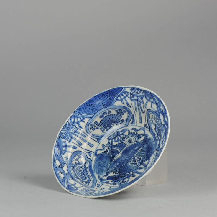 17C Ming/Transitional Chinese Porcelain Klapmuts Symbols Mask  1605-1650 Bowl or klapmuts on a footring and a flat, slightly upturned rim with a scalloped edge. This klapmuts can be classified as a group V klapmuts according to Rinaldi. The mask is often referred to as taotie, on of the oldest symbols used in Chinese decoration. It was represented as early as the Shang Dynasty (1600-1100) BC on bronze and later on jade.