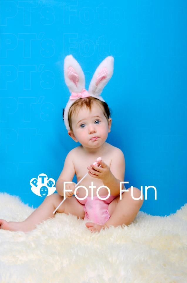 Little girl with pink bunnie rabbit ears and blue background