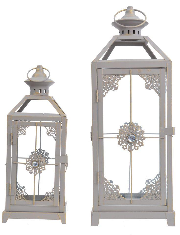Komplet 2 metalowych latarni w kolorze beżowym, ażurowe z uchwytami, przecierane z ozdobnymi kamieniami. Latarnie o wysokości 34 i  46 cm. Idealne do dekoracji i wystroju wnętrza w domu lub w ogrodzie. Cena dotyczy kompletu 2 szt.