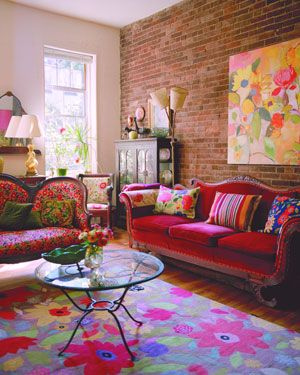 The living room is brightened by many of Kim's designs - in the form of cushions, paintings and a large rug.