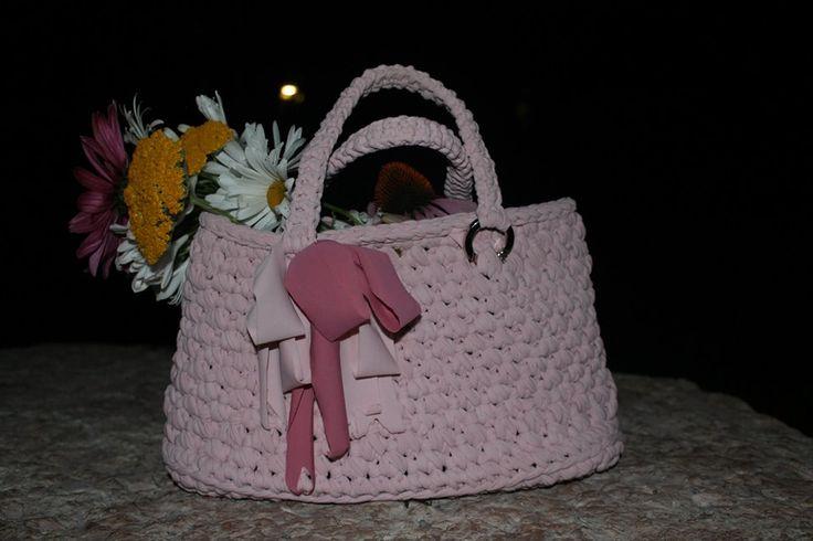 Borsettina rosa pallido, elegante poggia su una pietra. Anche manici fatti di fettuccia.