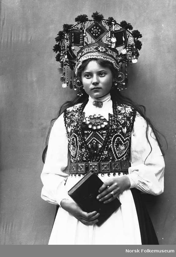 Digitalt Museum - Studiofotografi av kvinne med brudedrakt og brudekrone. Stående med salmebok/bibel i hånden. 3/4 dels utsnitt. Vendt mot høyre. Ser ut av bildet.