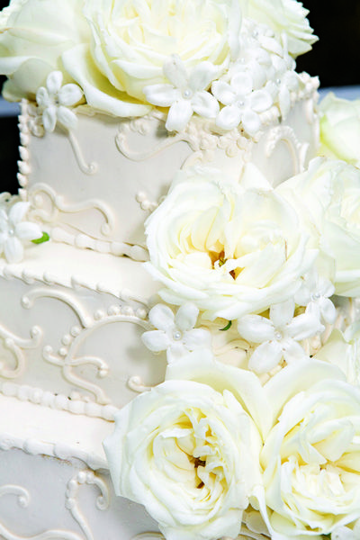 A mix of sugarpaste and real roses accent this pretty cake