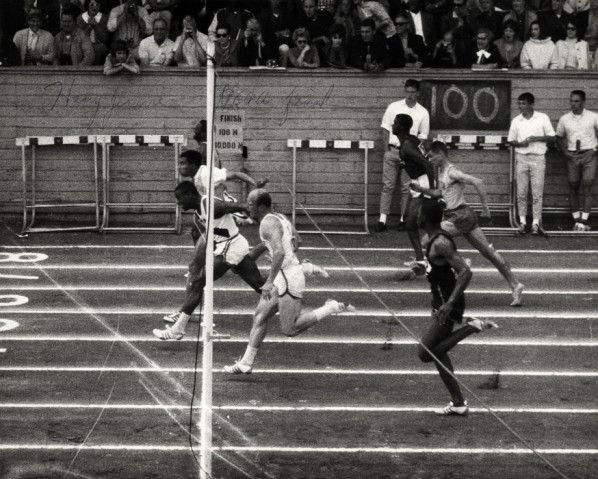 Black and white photo of the finish of the 100-yard dash at the1964 NCAA track and field championships held at Hayward Field and won by the University of Oregon's Harry Jerome. ©University of Oregon Libraries - Special Collections and University Archives