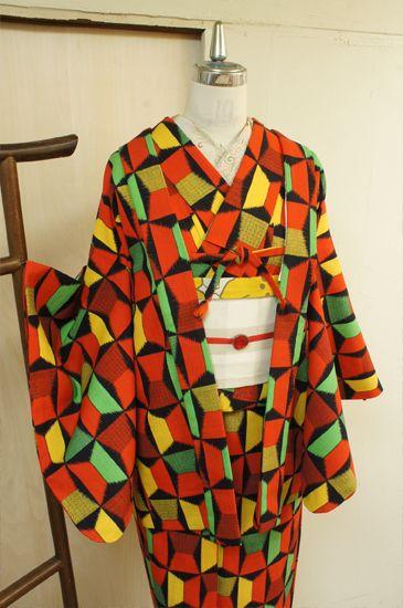オレンジ、黄色、グリーンの、ブルーナの絵本のような、昭和レトロポップな広告デザインのようなノスタルジックなカラーで織り出されたリボンのようなジオメトリックパターンがとびきりキュートなウールのアンサンブル(羽織と着物のセット)です。