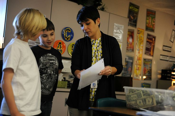 "Fifth grade teacher Laura Sebastian shares the results of a ""quarter war,"" a weeklong schoolwide event that raised funds for the Wounded Warrior Project, Dec. 17 at Remington Elementary School in Falcon School District 49. Fifth graders Logan Duncan, 10, and Logan Nestelroad, 10, spent time after school the past week to count each classroom's donations and make deposits."