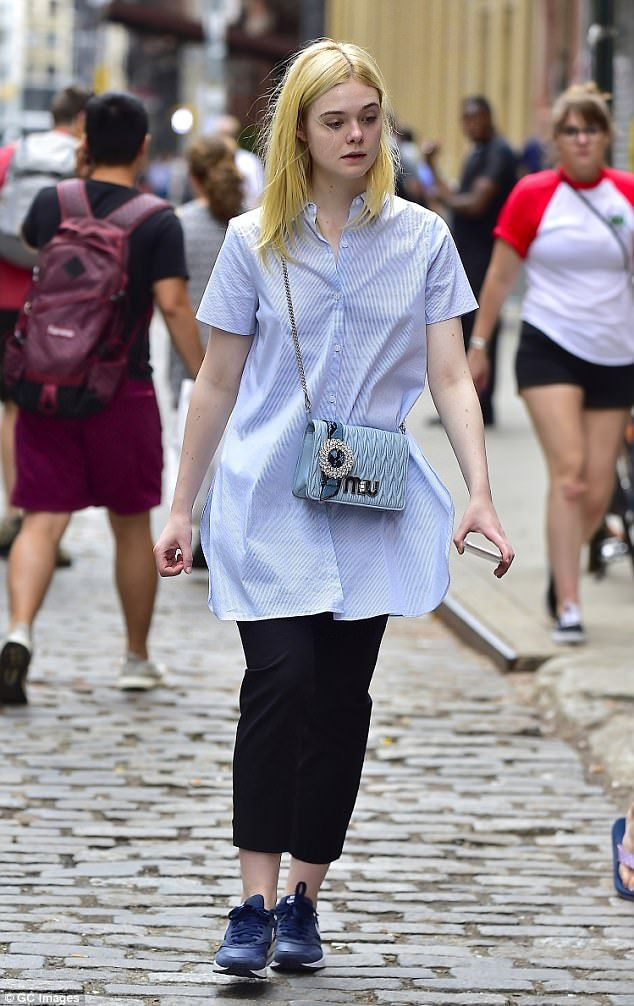 Coordinated look: The actress paired a pale blue shirt dress with black pants and dark blue Nike trainers as she hit the streets of Soho with a bejeweled Miu Miu purse