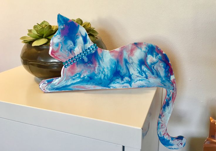Poured paint on a wooden cat. He sits on your door frame.