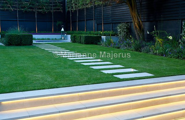 Spa Garden | Lit steps and stepping stones leading across lawn to terrace with spa | Charlotte Rowe Garden Design
