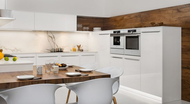 Kuchyně LINE, kde dominuje bílý lesklý lak jako hlavní materiál v doprovodu rustikální dýhy dubu selského. Kromě výrazné úchytky si všimněte i obkladu stěny