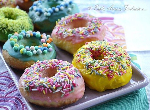 Queste coloratissime ciambelle americane sono rigorosamente cotte al forno, quindi non fritte come previsto dalla ricetta originale. Sono le preferite da Homer Simpson ed è impossibile non innamorarsene! Sono soffici, con tante glasse colorate e codette che le rendono ancora più belle e gioiose per la vista!