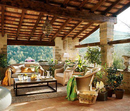 En plena naturaleza  El porche se integra en el paisaje. Alfombra, mantas bordadas en la India y cojines de lino. En Coco-Mat.