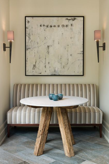 In a dining nook, a wide bench seat that fills the entire back wall will create the look of an ample private booth, whereas many individual chairs might create the look of a too-cramped dining room. (by Andrew Roby General Contractors)