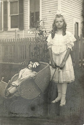 Charming antique photo of young girl with doll in a wicker baby buggy/pram, circa 1910