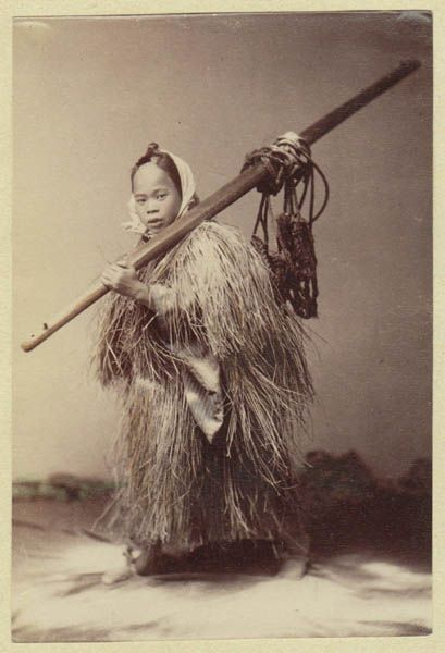 Antique Japan Photograph: Albumen studio-photo, thin paper, fixed on paper with small glue spots at he corners. The photo depicts a young Japanese man, dressed with a mantle made of straw and carrying a wooden pole with cords