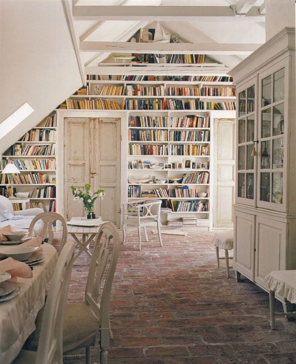 This library covers one very large gable wall of an attic loft in Sweden. The very white walls and furnishings reflect traditional Swedish design and the roughly-hewn brick floor looks quite ancient.