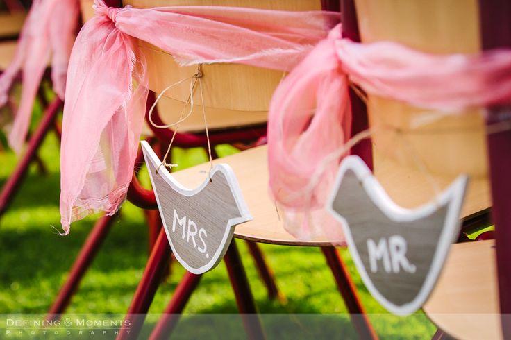 Detail van roze tule strikken en kleine bordjes in de vorm van vogeltjes met de tekst 'Mr.' en 'Mrs'. Leuk idee om aan te geven welke stoelen voor het bruidspaar zijn, en niet alleen tijdens een tuinbruiloft!