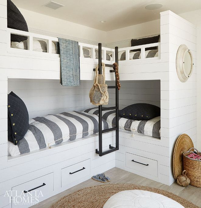 Coastal Farmhouse Bunkroom with shiplap paneling. L-shaped bunkbeds. The bunk room, which sleeps four, features l-shaped bunkbeds, white shiplap siding and coastal-inspired linens. Coastal Farmhouse Bunkroom with shiplap paneling. L-shaped bunkbeds. The bunk room, which sleeps four, features a l-shaped bunkbeds, white shiplap siding and coastal-inspired linens #CoastalFarmhouse #CoastalFarmhouseinteriors #CoastalFarmhouseBunkroom #FarmhouseBunkroom #Coastalbunkroom #shiplap #shiplappaneling…