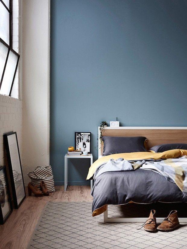 Quarto de casal com parede azul grafite, tapete geométrico e piso de madeira