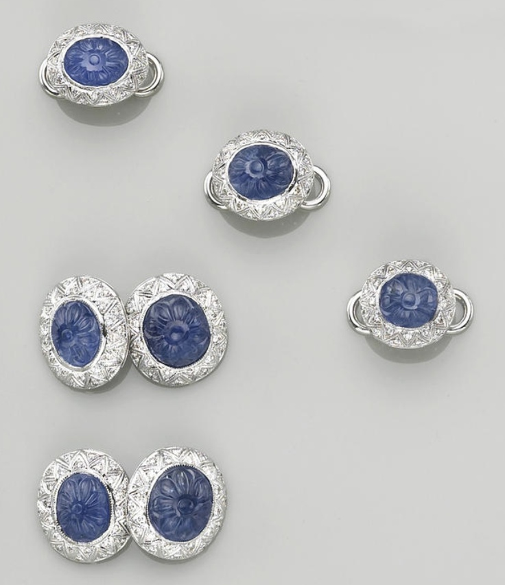 A sapphire, diamond and eighteen karat white gold dress set  comprising a pair of cufflinks and three shirt studs, each centering a carved cabochon-cut sapphire, surrounded by a geometric pattern of round brilliant-cut diamonds