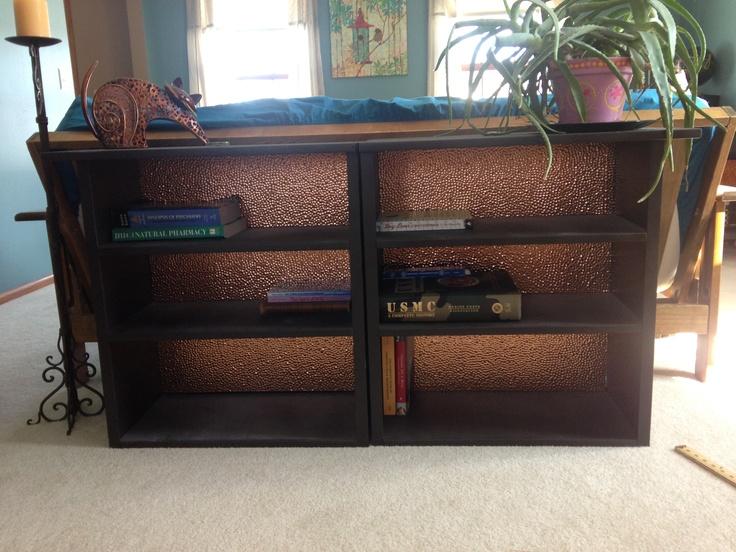 Bookcase embellished with Fasade backsplash panel in Hammered, Polished Copper.