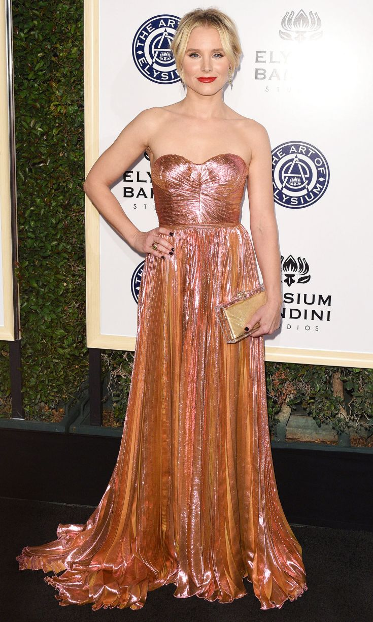 KRISTEN BELL wears an iridescent pink gold strapless pleated Maria Lucia Hohan gown with a golden clutch to the Art of Elysium Gala.
