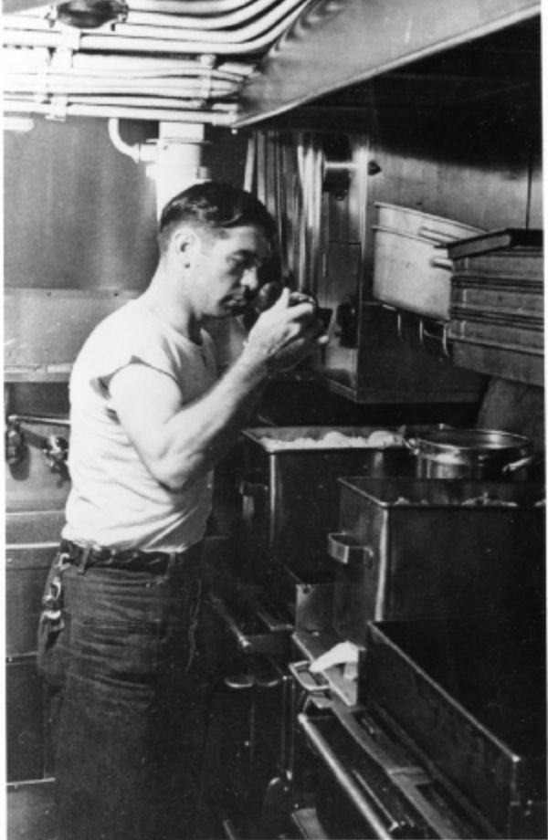 Merl Crosbie samples a meal in the Silversides' galley. circa WWII