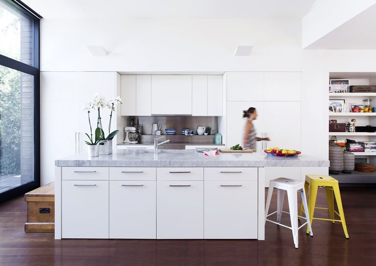 """A chunky Carrara marble benchtop cantilevered on one end is the showpiece element of this white kitchen in a [renovated Victorian cottage](http://www.homestolove.com.au/victorian-cottage-renovation-2586