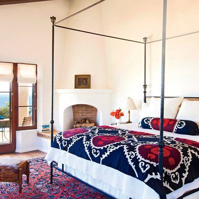 A richly colored rug and a vibrant suzani pattern on the bed's quilt and bolster pillow bring warmth to the airy master bedroom that opens onto the terrace and its spectacular Pacific Ocean vistas.