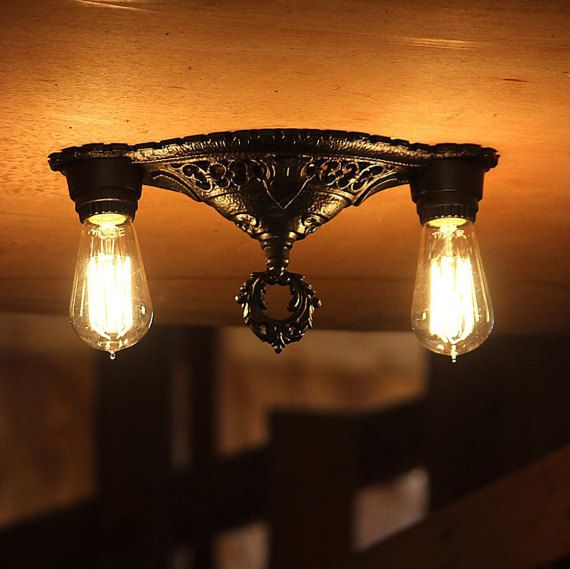 A sleek antique ceiling light made of iron. The flush mount down light was made in the early 1900s in the United States and is perfect for a low