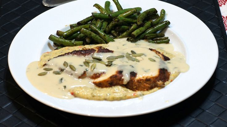 Ancho Crusted Chicken Breast atop Green Chile Goat Cheese Grits Topped with a Cilantro Cream Sauce and Roasted Pipitas