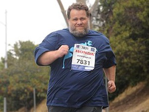 """Weighing in at 400 pounds, Kelly """"Man of Fat Steel"""" Gneiting is both a three time U.S. sumo wrestling champion and an award-winning marathon runner. In 2011, he set a Guinness World Record for being """"Heaviest Person to Complete a Marathon (LA Marathon, 2011)"""""""