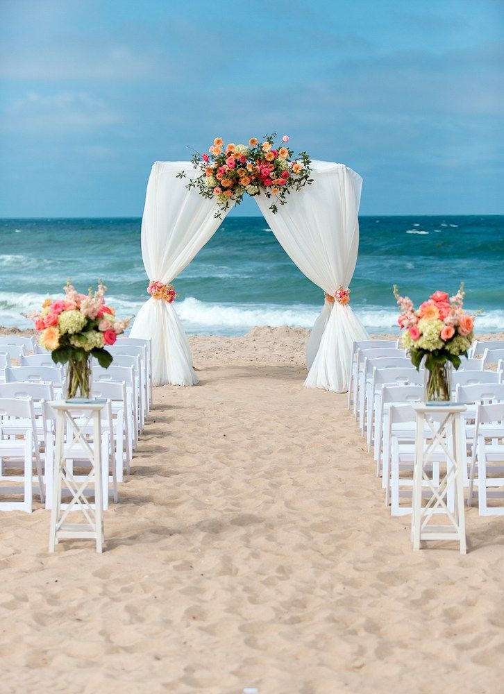 Beautiful arch and flowers at this beach wedding ceremony. Jennette's Pier Wedding / Outer Banks Wedding / Photo by Digital Wunderland #jennettespierwedding #outerbankswedding #jennettespier #obx #nagsheadwedding https://www.digitalwunderland.com/wedding-photography/