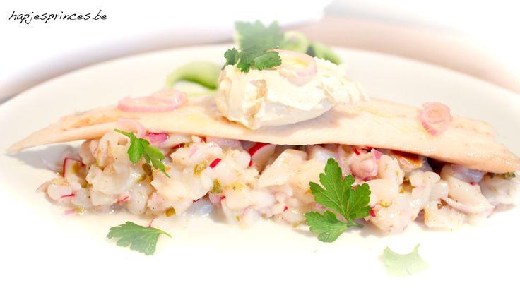 Deze tartaar van sint-jakobsvruchten met gerookte paling is een recept van Claudia Allemeersch. Heel lekker voorgerecht die je perfect op voorhand kan klaarmaken.