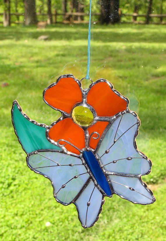 Disfruta de primavera todo el año! Mariposa de color azul y una flor naranja en vidrio de color. Alambre y soldadura de acentos en las alas de las mariposas añadir textura e interés. Tenue cristal transparente se utiliza en este original diseño suncacther. Los colores son azul claro, verde y naranja con alambre de plata y estaño. Cuelga por un cordón adjunto y es de 4,5 pulgadas de ancho por 5 pulgadas de alto. Aclarará cualquier ventana cuando el sol brilla a través. Cada una de estas…
