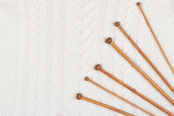 wooden knitting needles on white knitting wool texture background
