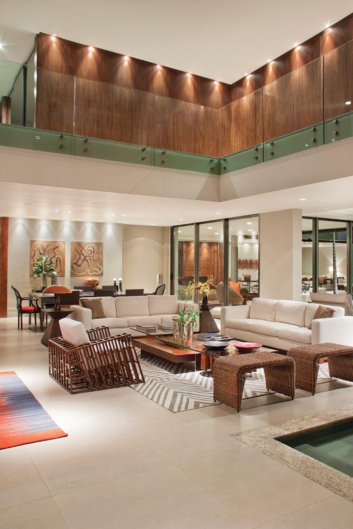 """O living com espelho d'água foi """"vestido"""" com tapetes estampados (Gallery Tapetes), móveis em fibras naturais e madeira (Quadra Design e Artefacto)."""