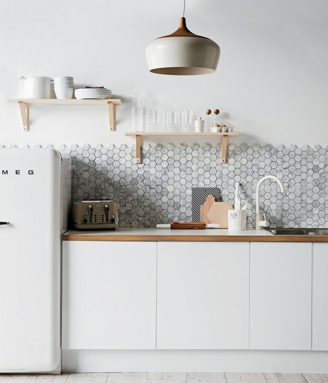 A backsplash of hexagonal Carrara marble from Australia's Di Lorenzo Tile offsets the minimalist cabinetry in this kitchen styled by Jack...