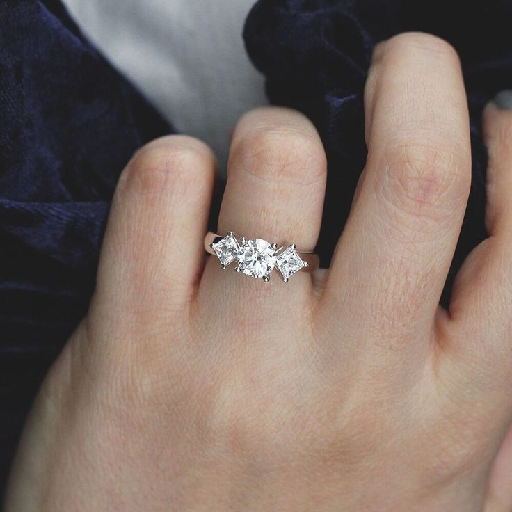 The April Engagement Ring takes three stone rings to a new level. It features a center stone of your choice set between two kite-set Princess Cut Diamond Hybrid® side stones.
