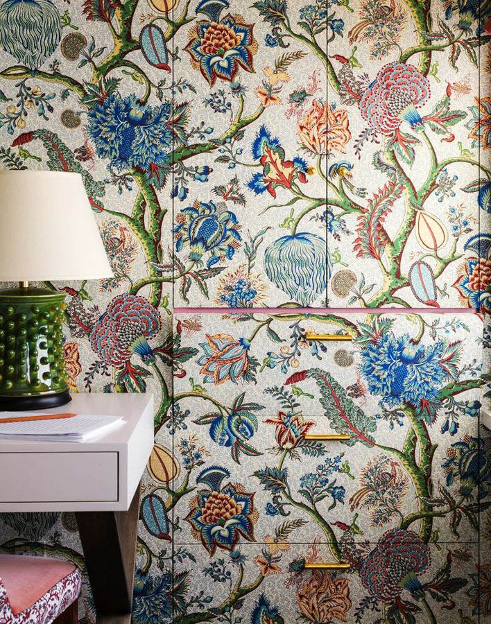 clever clever clever way to make furniture unobtrusive... cover it with the same wallpaper as the rest of the room!