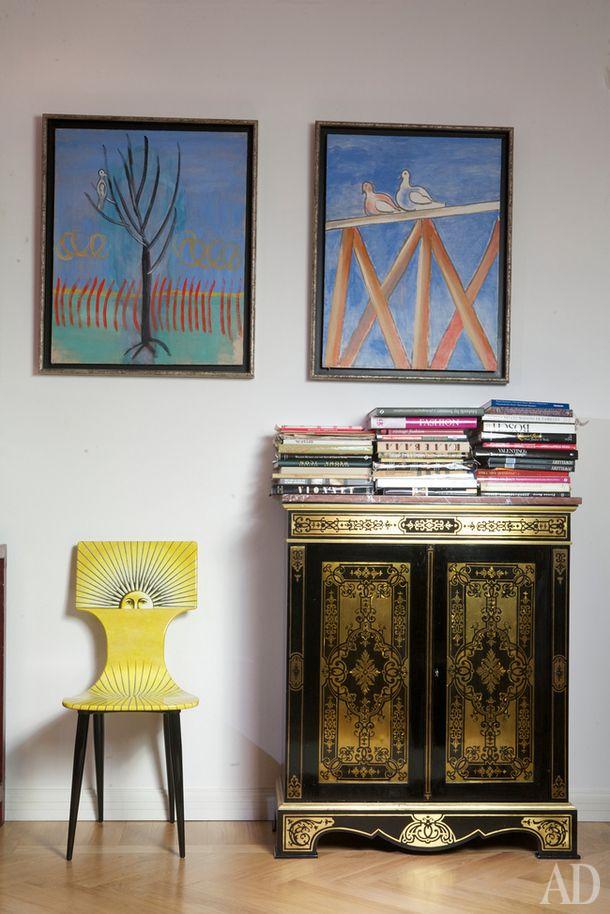Лаковый антикварный комод соседствует со стулом Fornasetti. На стене — картины…
