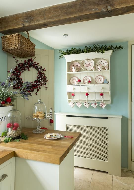 Love the whire shelf with red dishes and greenery on top