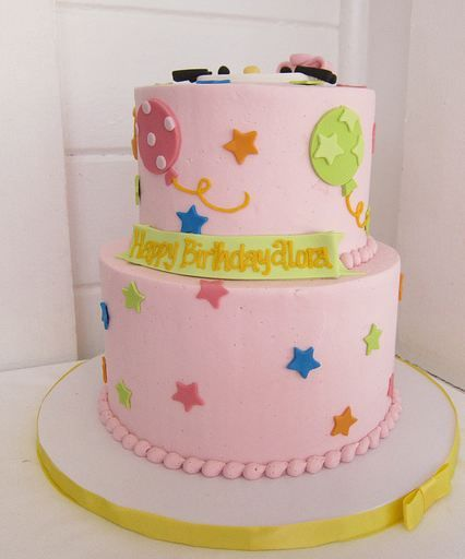 Two tier pink round birthday cake with stars and balloon ...