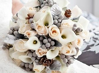 Winter wedding flowers, I love the contrast if the grey snowberries against the creams and peach flowers